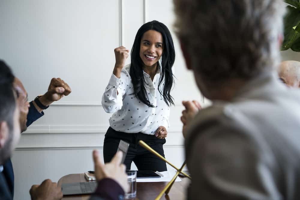 Businesswoman motivating her team members in a meeting